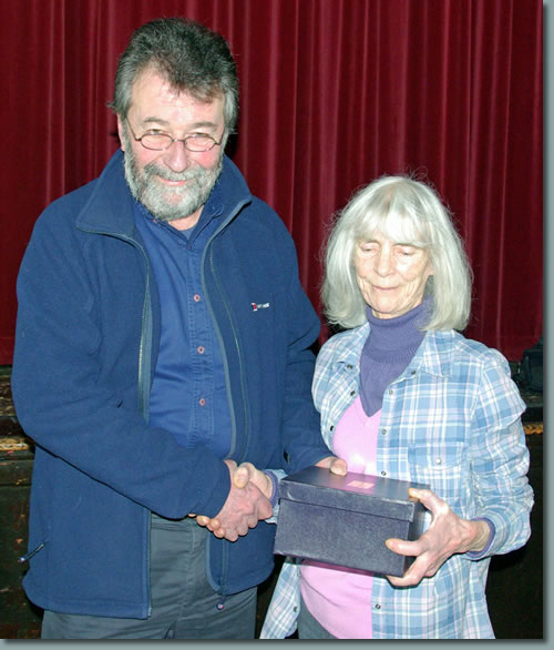Eric Robson presents Colleen Harrison with an inscribed cut-glass bowl in recognition of her many years of 'backroom' service to the Society
