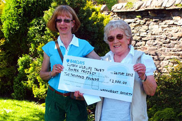 Photograph: Caroline Nichol (left) presents a cheque to Susan Garnett (right)